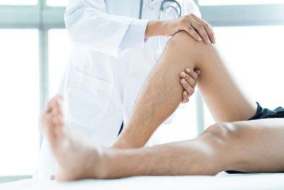 medico di ortopedia cura la gamba del paziente a milano