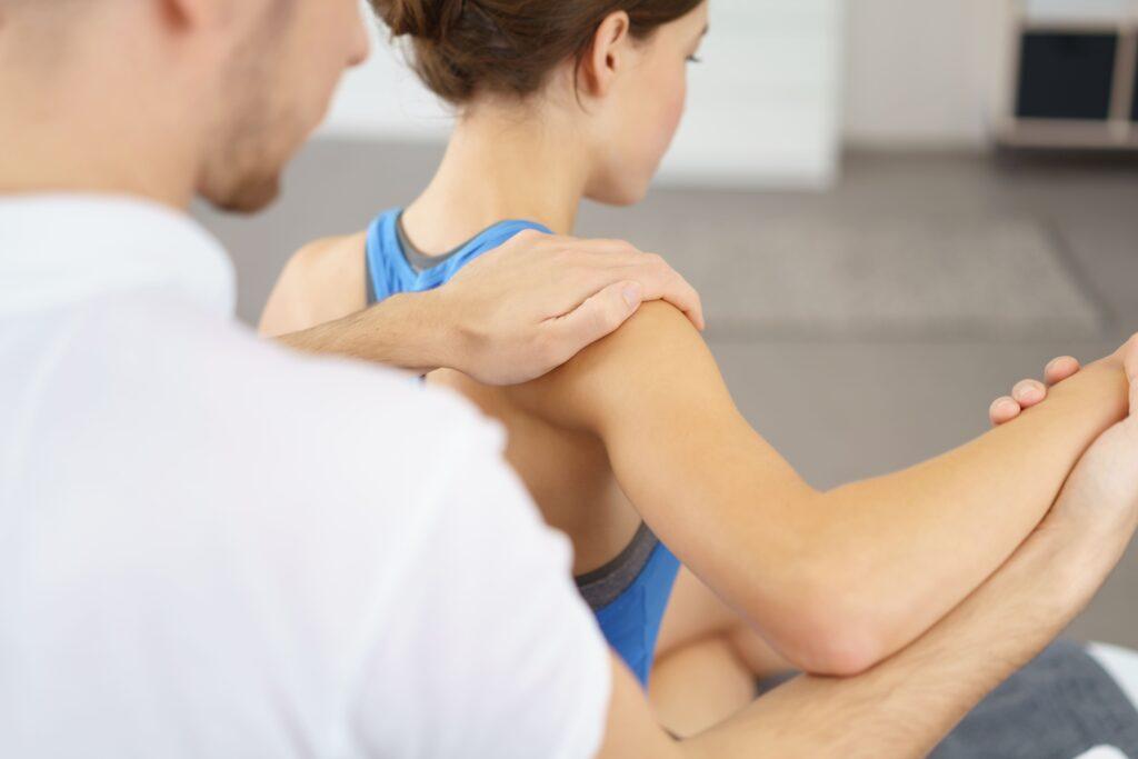 Donna giovane durante un trattamento di fisioterapia per la spalla dolorante